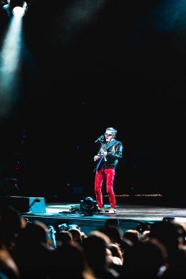 Muse frontman Matthew Bellamy singing alone, centerstage under a spotlight. Photo: Lmsorenson.net
