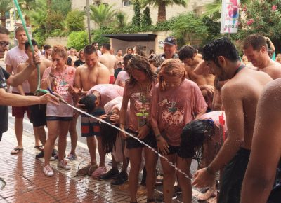 As is customary with La Tomatina, the locals are kind enough to hose us down after we have painted their town red with the blood of the tomato projectiles. Photo: Talyn Sherer