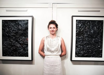 Artist Ali Mitchell, pictured with work from her Oil Fields exhibition at Mestizo Coffeehouse. Photo: Blake Peterson