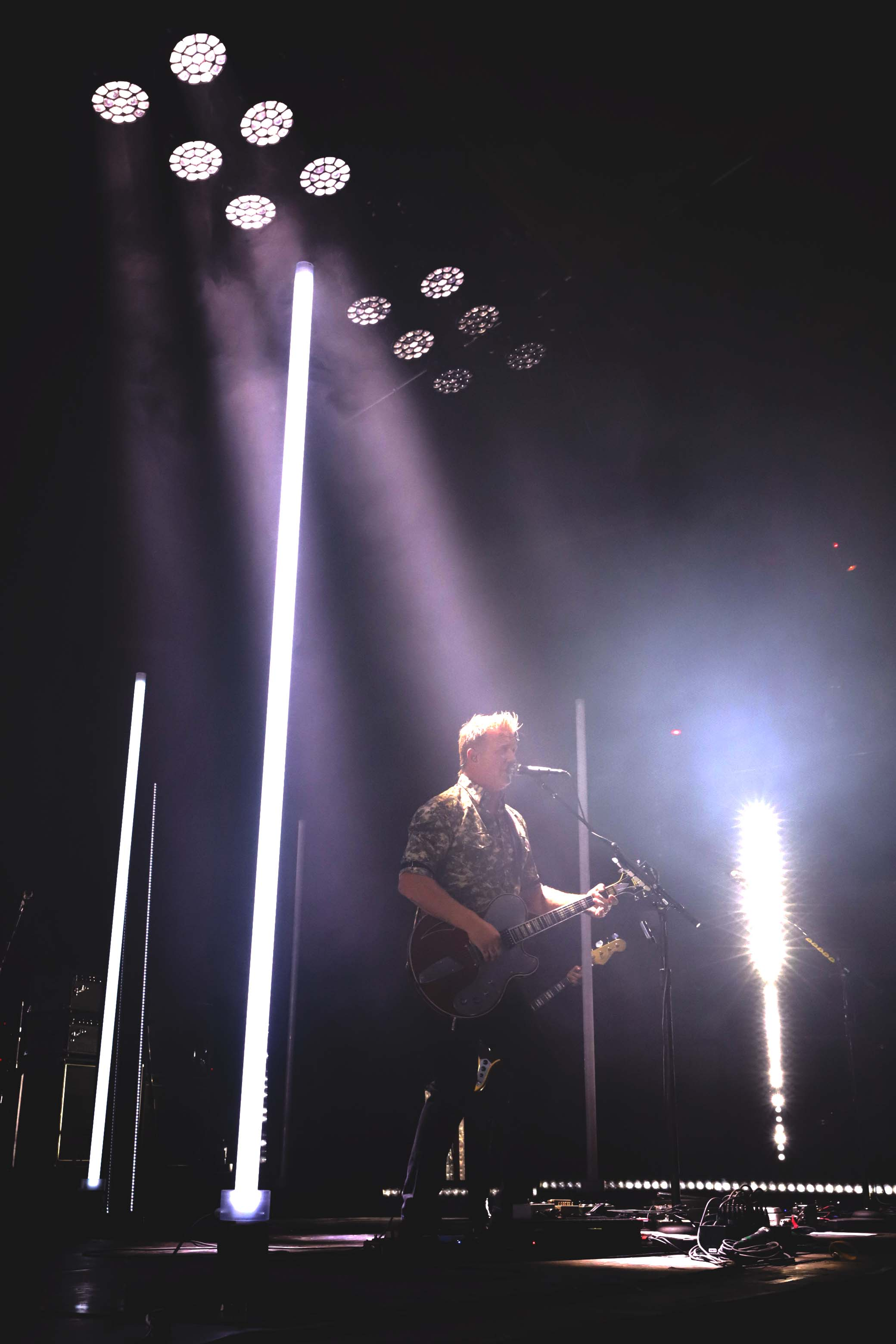 Lead singer Josh Homme stands stage right with a beam of spotlight over him as he provides vocals. Photo: Lmsorenson.net