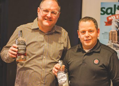 (L–R) Jeff Thompson, grand ambassador, and James Fowler, owner, of Sugarhouse Distillery show off their whiskey varieties that set them apart from others in the local industry. Photo: Talyn Sherer