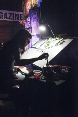 Mataya Maxfield working on a painting just left of the stage in Urban Lounge. Photo: Will Cannon