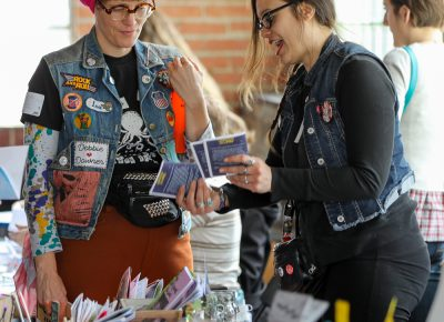 (L-R) Amy Lou from Wasted Ink Zine Distro in Phoenix and Andy Cooper from Viva Vox Press in Tempe talk zines and buttons at Grid Zine Fest at Publik Coffee on April 14.