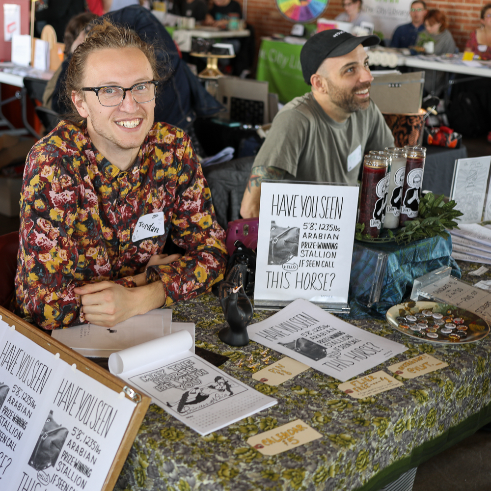 (L-R) Jordan Youngberg and Jordan Duke called their table Maurice von Margoza and Associates™. Youngberg is from Provo, and his horse-themed offerings drew a steady crowd.