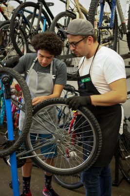 (L–R) Elijah Lowe and SLC Bicycle Collective Education Coordinator Kaden Coil-Pittman work on a mountain bike via the Collective's revamped youth-education program. Photo: John Barkiple