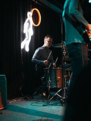 Dacus's neon incarnation of her album artwork illuminating drummer Ricardo Lagomasino.