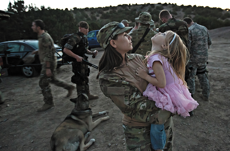 """USM member Lindsay Wood holds her daughter, Rory, during a field training exercise in rural Utah. """"We're normal. I do the same things as you. On my Facebook I still post pictures of my cats and dinner and everything else. It's not like all I'm focused on is this crazy training. It's a normal life; we just have another aspect to it,"""" says Wood."""