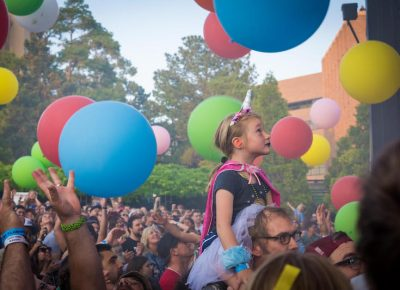 A young fan watches the show as colorful balls dance in the sky. Photo: ColtonMarsalaPhotography.com