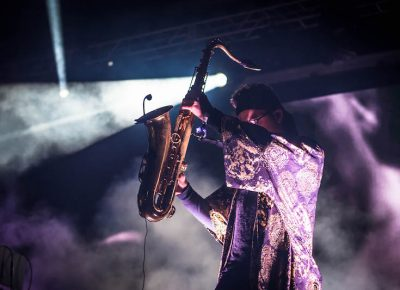 Dramatic light strikes the saxophone player of ZHU.