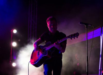 Dramatic stage light plays with guitarist.