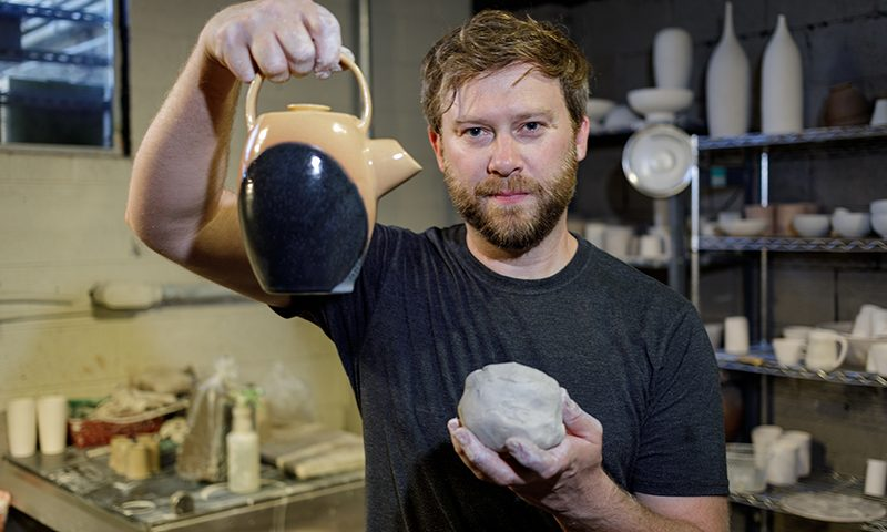 Sudweeks proudly holding up his pottery. Photo: John Barkiple