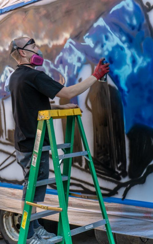 Local artist Just242 painting a mural of SLC. Photo: Randy Roberts