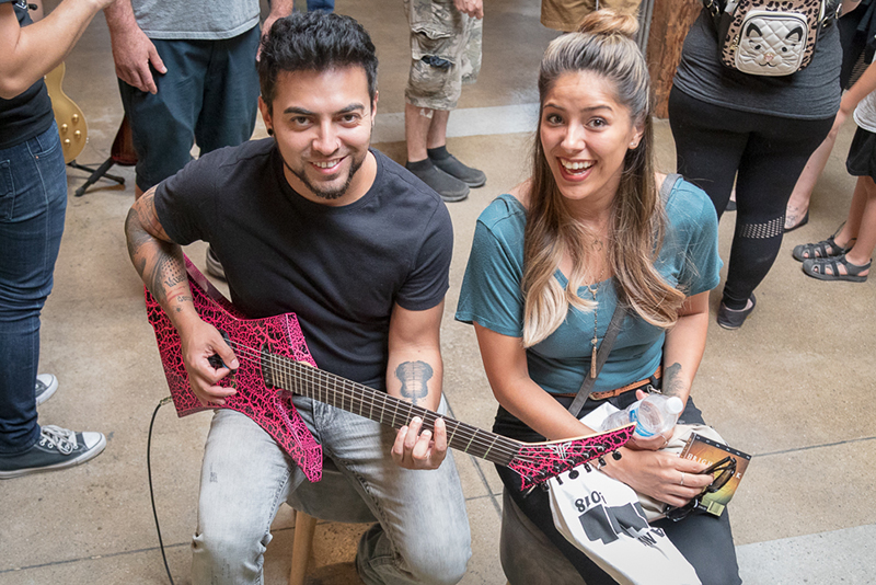 "(L–R) Randy Perea and Mireya Medina take a look at Rob Gray's pointy guitars. After playing, what does Perea like? ""The color, of course."" Gray builds multi-scale and extended-range seven- and eight-stringed guitars, and he likes 'em colorful and pointy."