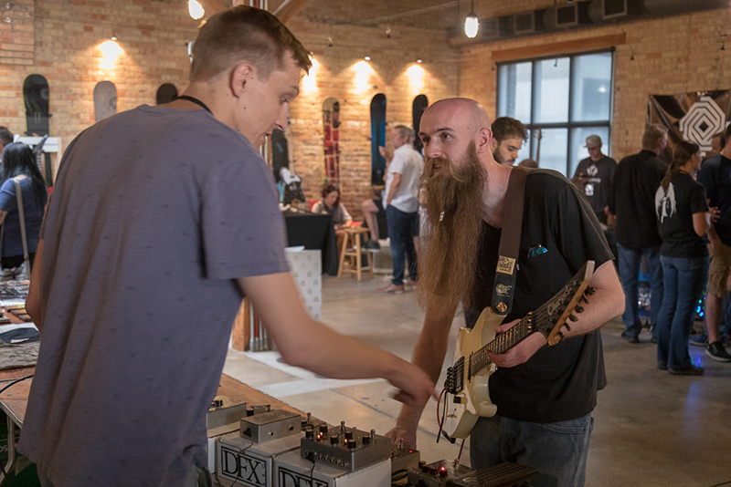 "(L–R) DFX's Brad Burnell points out features of the ""F.M. Fuzz"" effects pedal while Tyler Gipson takes it for a spin. Gipson plays in Esther Lane and has a solo project called Weasel Fever that's pure metal."