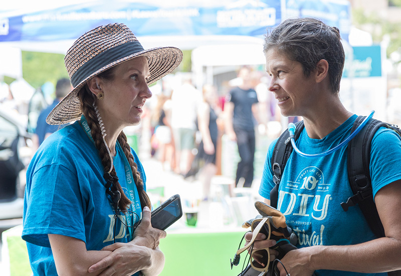 (L-R) Craft Lake City Executive Director Angela Brown and Production Volunteer Aimee Horman discuss installation options for the misters on the VIP Lounge at Craft Lake City's Tenth Annual DIY Festival.
