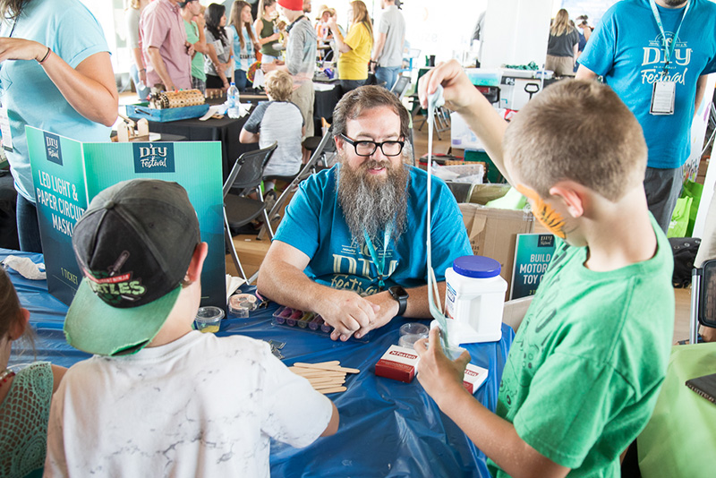 Craft Lake City STEM Craft Assistant Peter Reed helps pint-sized inventors stir up cup-sized portions of DIY slime.