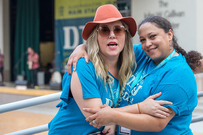 (L-R) Craft Lake City Entertainment Coordinator Kellie Call and Production Volunteer Danielle Turner embrace on the Gallivan Plaza bridge. Call split her time between the SLUG stage and the KRCL stage as she checked on DIY Festival performers.