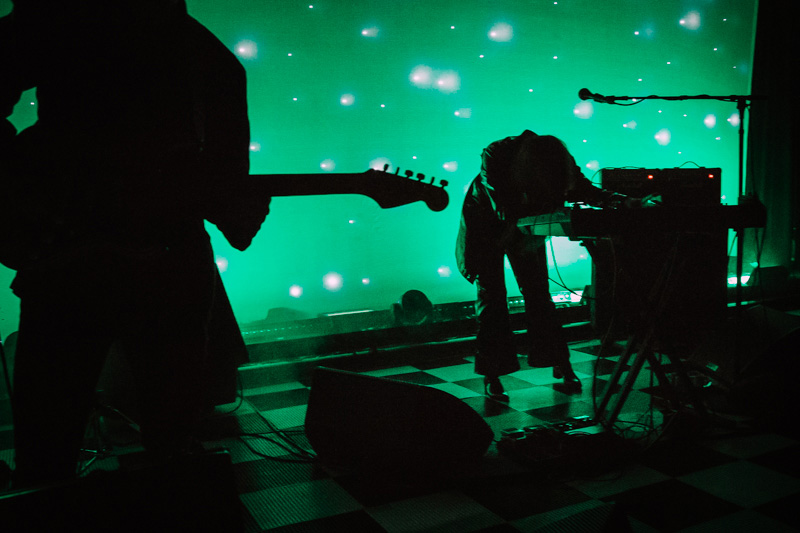 Beach House performing in a sea of green.