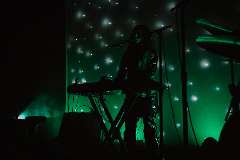 Side stage lighting and a starry green scrim surround Legrand as she performs.