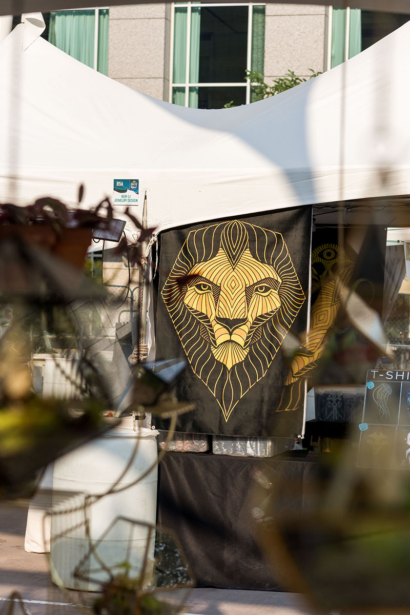 A giant lion tapestry hangs from the booths.