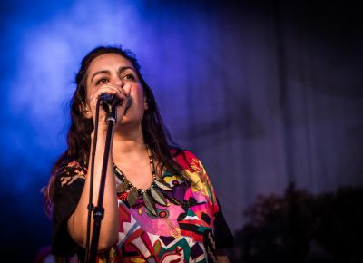 Ariel Engle sings in the bright stage light of blues and purples.