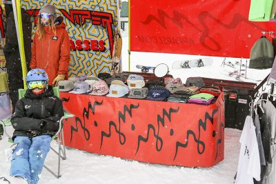 IZM apparel booth has hats and t-shirts on display.