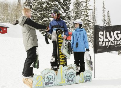 Winners of the mens 17 & under snow show good sportsmanship on the stand. 1st place Isaac Harkness shakes hands with 2nd place Greyson Hawkins, and 3rd place Noah Singer smiles in anticipation for to shake his fellows snowboarders hands.
