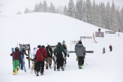 Skiers and snowboarders trek uphill.