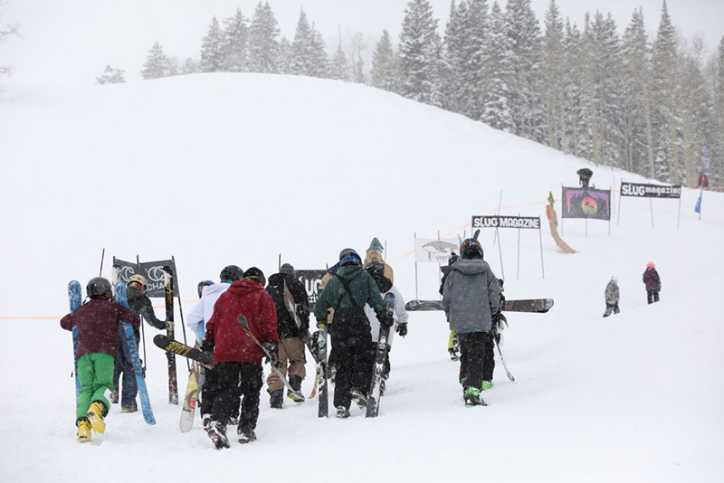 Skiers and snowboarders trek uphill.