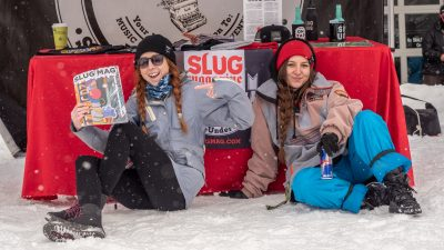 The SLUG sales team shows off their merch at the booth.
