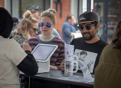 (L-R) Lily Godfrey and Wafiq Ali stock up on tokens as they grab their plastic steins at the entrance of Brewstillery at Trolley Square. They look forward to drinking beer in this nice weather. Photo: John Barkiple