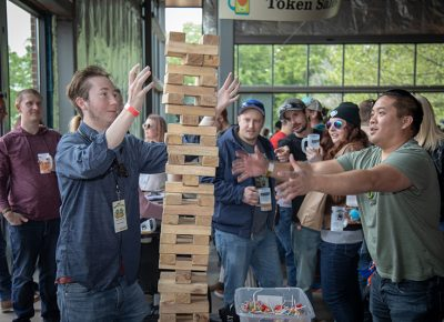(L-R) Kayden Corbett and Van Nguyen get into some Jenga while the crowd cheers them on at the Brewstillery main space entrance. Photo: John Barkiple