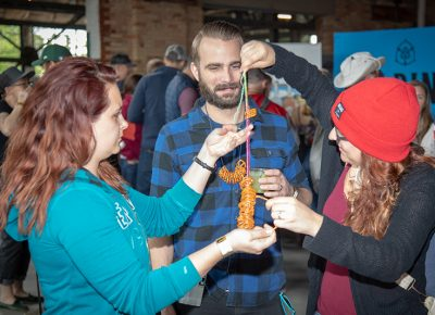 """(L-R) Briana Dalton with Chelley and Joe Coleman get their beer craft on at the Yelp pretzel table. """"I make the best necklaces,"""" Joe said. Photo: John Barkiple"""