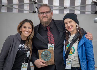 Ana Valdemoros and Angela H. Brown rewarding Holystone Distilling co-owner and distiller Ethan Miller with the People's Choice: Best Brewstillery Cocktail and Singular Contribution to Utah Spirits Awards. Photo: John Barkiple
