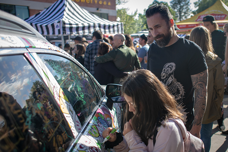 (L-R) Brian and Sosie Carlson put in some EXPO marker time on Mark Miller Subaru's Art Car. Sosie is satisfied with her green squiggley line. Photo: John Barkiple