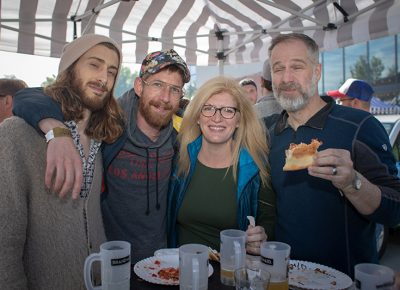 (L-R) Robbie Runyan, Nick James, Rebecca and Mark Arrington hide from the sun under an awning. Rebecca loves lots about Brewstillery: the location, the clear skies and the mix of food and beer. Photo: John Barkiple