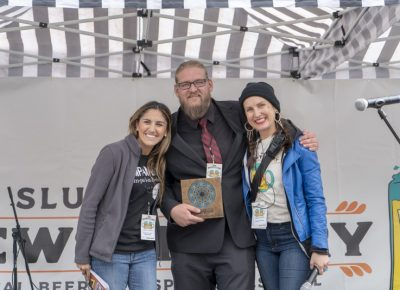 Ana Valdemoros and Angela H. Brown rewarding Holystone Distilling co-owner and distiller Ethan Miller with the People's Choice: Best Brewstillery Cocktail. Photo: Jayson Ross