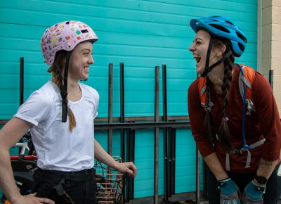 (L–R) Renée Draper and Marian Lewis share a pre-race joke. First time alley-cater and first-place finisher Draper heard about the race from her work pal, Scott Morely. That the alley cat is like a scavenger hunt appeals to her game-loving personality. Third-place finisher Lewis rode a rental in SLUG Cat 2019. She joined the race today because she loves the social aspect of a good bike gathering. Photo: Kaylynn Gonazlez