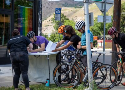 SLUG Magazine's Joelle B. signs racers up for a mailing list outside of Blue Copper Coffee during an early stop in the SLUG Cat. Photo: Kaylynn Gonazlez