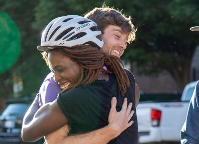 (L–R) Nkenna Onwuzuruoha hugs Davey Davis. She mis-mapped her manifest, so she didn't reach the podium, but she still finished with a smile. Davis handicapped himself in today's race by riding SLUG's old beater bike. Photo: Kaylynn Gonazlez