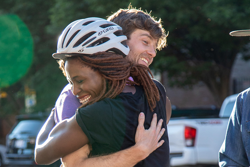 (L–R) Nkenna Onwuzuruoha hugs Davey Davis. She mis-mapped her manifest, so she didn't reach the podium, but she still finished with a smile. Davis handicapped himself in today's race by riding SLUG's old beater bike. Photo: Kaylynn Gonazlez