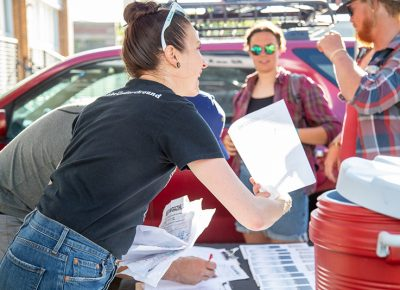 SLUG Magazine's Angela Brown collects manifests as SLUG Cat racers arrive at SLUG HQ, where racers receive Fat Tire apparel and New Belgium Brewery water bottles. Photo: Kaylynn Gonazlez