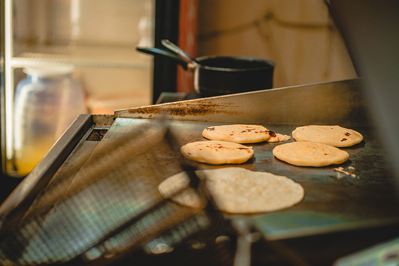 El Viroleño's nearly-finished pupusas on the grill.