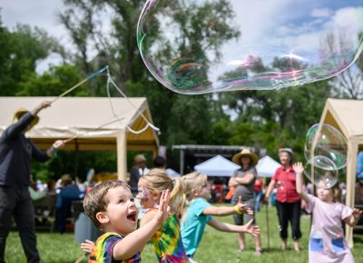 A young fan chasing a bubble.