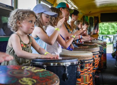 The young folks take part in drum bus sessions.