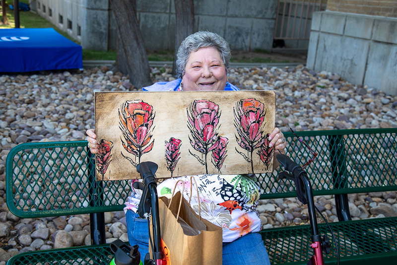 "Paula Miller holds a painting purchased by her daughter. ""If she sees something she likes, she has to have it,"" Miller said."