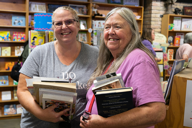(L–R) Meg Drage and Maire Nelligan fill their arms with books. Drage, ironically, has a book on back health at the top of her heavy stack.