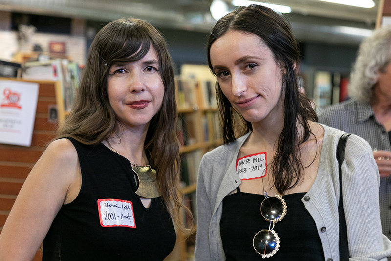 "(L–R) Stephanie Leitch and Kylee Hill have both worked as Weller Book Works employees. Hill (2018–19) thinks that her bookstore colleagues are great. Leitch is closing in on her second decade in the store. ""I am the person I am today because of the store,"" Leitch said. She's an artist and sculptor, and her mind has expanded due to all the ideas and people she has encountered over the years."