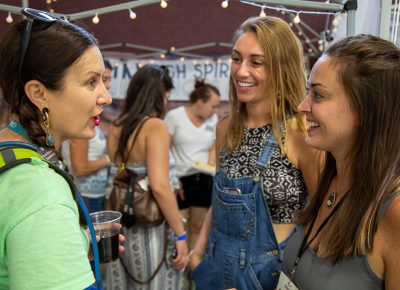 (L-R) In the Makers Building, Angela Brown chats with Mallory Kidwell and Claire Sessler, the owners of In High Spirits Infusions, to discuss possible workshop opportunities after a successful debut at Craft Lake City.