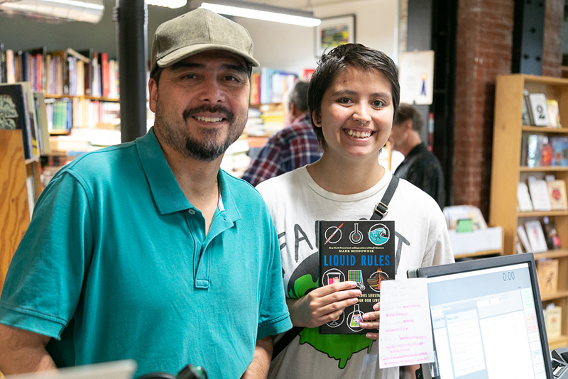 (L–R) Victor and Sophia Gener pick up a copy of Liquid Rules. Sohia is interested in science, and she starts her college career at the University of Utah in a week.